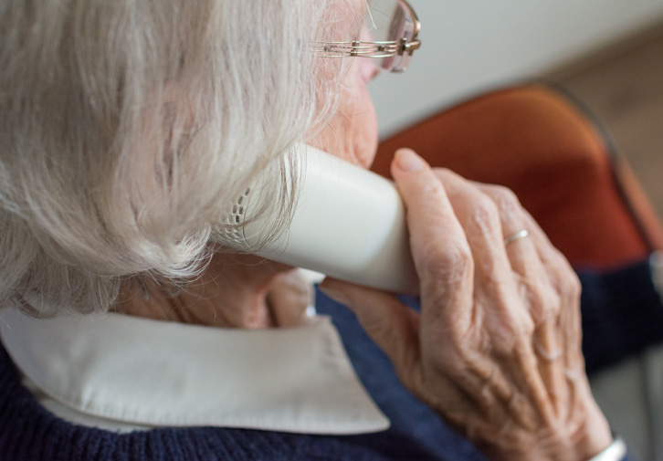 elderly woman on phone with medicare scammer